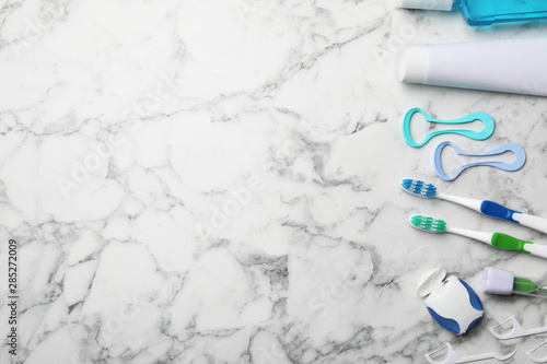 Fotografie, Obraz  Flat lay composition with tongue cleaners and teeth care products on marble background