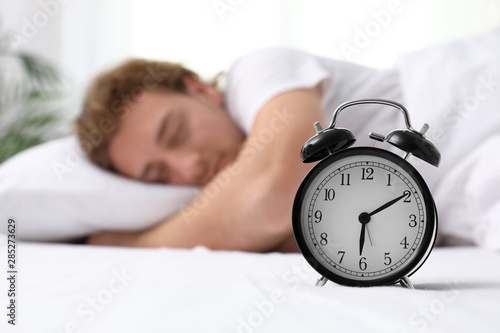 Fototapeta  Alarm clock and blurred sleepy man on background, space for text