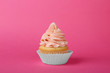 canvas print picture - Tasty cupcake decorated with cream on pink background