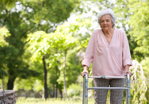 Elderly woman with walking frame outdoors. Medical help Canvas Print