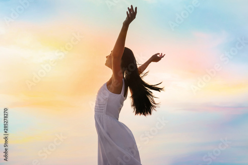 Young woman enjoying summer day against sky. Freedom of zen