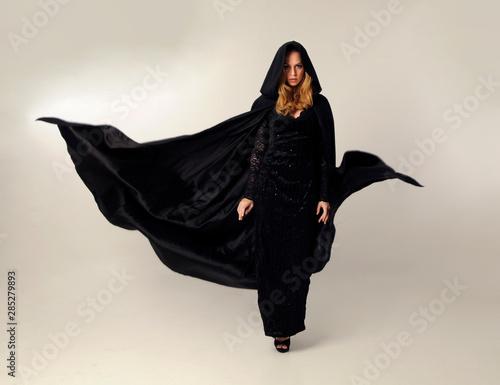 Fototapeta premium pełnej długości portret kobiety blondynka na sobie długi czarny zegar płynący i koronkową suknię, pozie stojącej na kremowym tle studio.