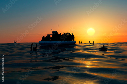 Refugees on a big rubber boat in the middle of the sea that require help Wallpaper Mural