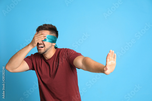 Photo Young man with blindfold on blue background