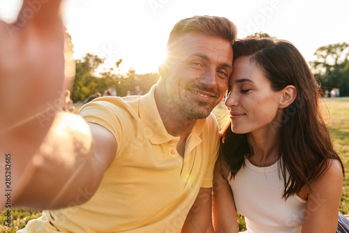Fototapeta Smiling cute adult loving couple outdoors in a beautiful green nature park take a selfie by camera. obraz na płótnie