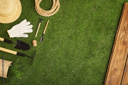Foto op Aluminium Tuin Set of gardening tools on green grass, flat lay. Space for text