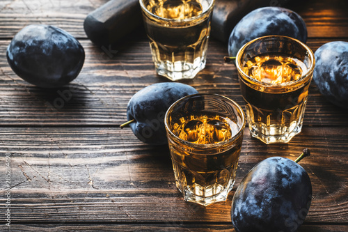 Photo sur Aluminium Bar Slivovica - plum brandy or plum vodka, hard liquor, strong drink in glasses on old wooden table, fresh plums, copy space