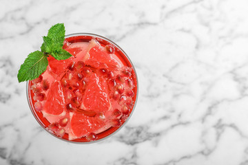 Glass of tasty refreshing cocktail with grapefruit and pomegranate on white marble background, top view. Space for text