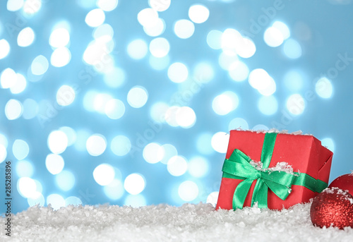 Obraz Christmas decoration and gift box on snow against blue background - fototapety do salonu