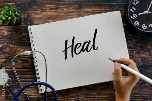 Stampa su Tela  Top view of stethoscope,plant, clock and hand holding pen writing Heal on notebook on wooden background