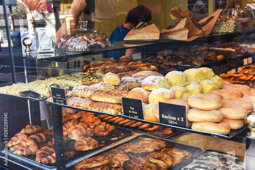 Display window of a bakery and pastry shop with assortment of different kinds of freshly baked artisan food. Authentic urban atmosphere