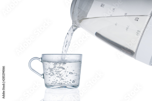 Valokuvatapetti Pouring hot water from an electric kettle in cup isolated on white background