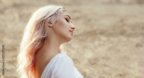 Fotografiet  head profile of young beautiful woman on a background of dry grass sitting on gl