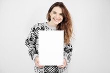 Attractive Happy Young Woman Wearing Christmas Sweater Holding A Blank Canvas In Her Hands.