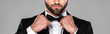 cropped view of elegant man in black suit fixing bow tie isolated on grey, panoramic shot