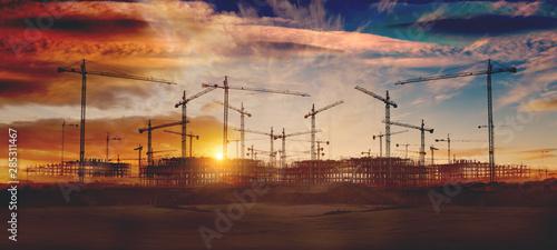 Obraz Gruas de construcción y puesta de sol.Concepto de industria y mercado inmobiliario..Cimientos de bloque de pisos - fototapety do salonu