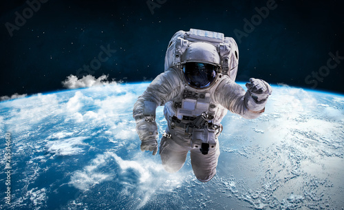 Astronaut in the outer space over the planet Earth. Clouds on background. Spaceman. Elements of this image furnished by NASA