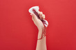 canvas print picture - partial view of woman squeezing sanitary towel with blood on red background