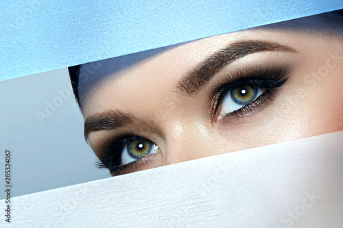Fényképezés  A girl with beautiful green bright eyes with brown shadows and expressive eyebrows looks into the hole of colored paper