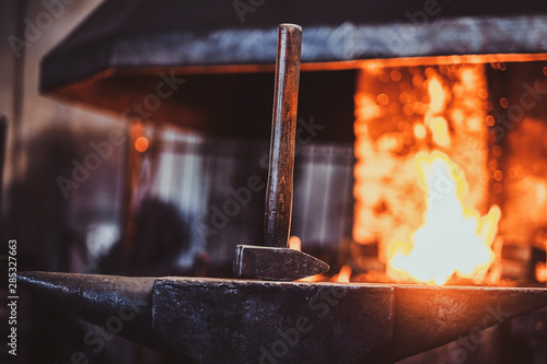 Wallpaper Mural Hammer on anvil at dark blacksmith workshop with fire in stove at background
