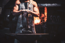 Muscular Blacksmith In Protective Apron At His Workshop With Hammer In His Hands. There Are Fire At Background.