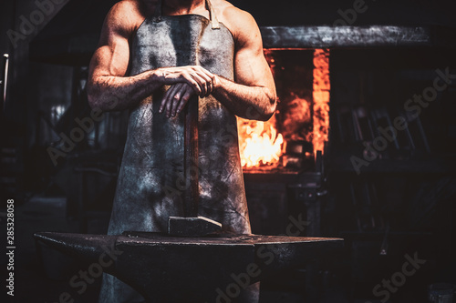 Muscular blacksmith in protective apron at his workshop with hammer in his hands Fototapeta