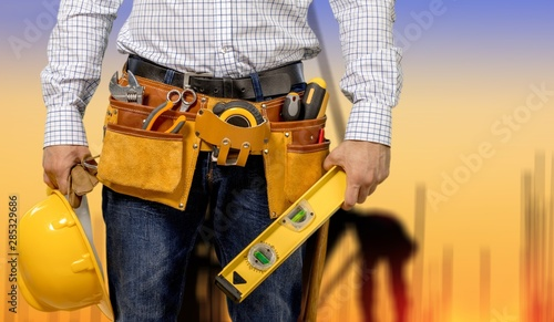Fotografía  Worker with a tool belt. Isolated over  background.