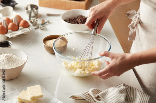 Cook preparing dough with butter and whisk.