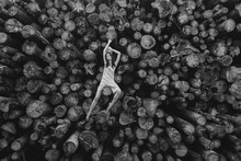 A Girl Is Sitting On A Woodpile.
