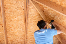 Volunteer Builder Drilling Into Roof Of House Under Construction