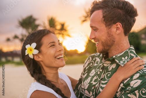 Happy couple lovers in love on romantic sunset beach vacation in Hawaii travel. Asian woman hugging Caucasian man smiling, interracial relationship. Newlyweds honeymoon or wedding on Tahiti beach.