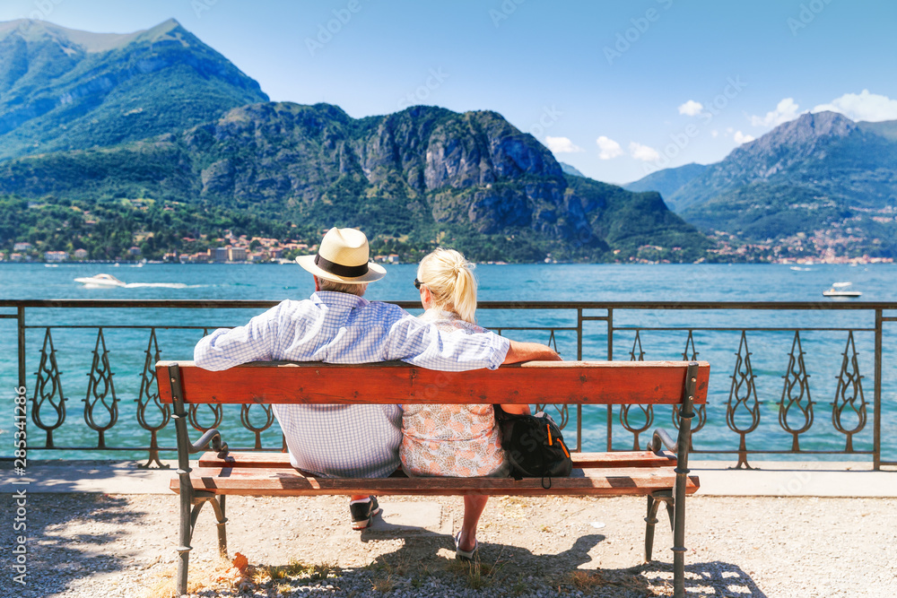 Fototapety, obrazy: Lake Como, village Bellagio, Italy. Senior couple weekend getaway having rest on the bench by spectacular lake Como in Italy. Sunny day scenery. Tourists admiring view on popular tourist attraction.
