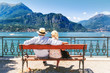 Lake Como, village Bellagio, Italy. Senior couple weekend getaway having rest on the bench by spectacular lake Como in Italy. Sunny day scenery. Tourists admiring view on popular tourist attraction.