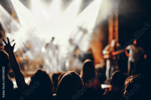 Silhouettes of concert crowd in front of bright stage lights. - 285346012