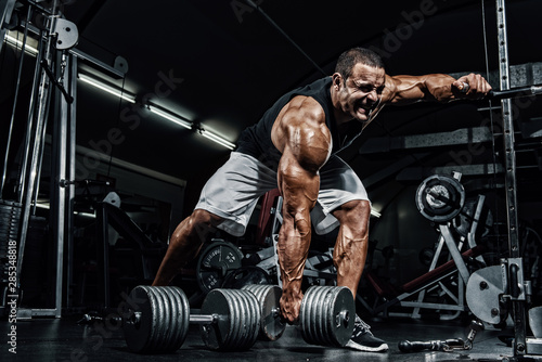 Hard Core Bodybuilding. Bodybuilder ready to lift heavy dumbbell Fotobehang