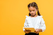 cute schoolchild with backpack holding book isolated on orange