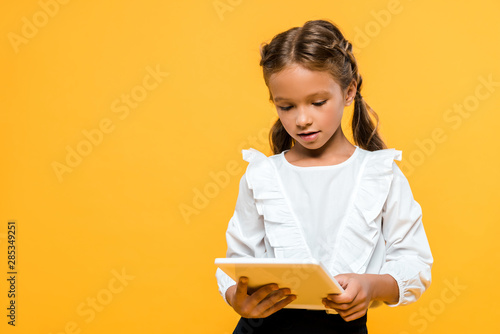 Fototapeta cute schoolchild with backpack holding book isolated on orange obraz