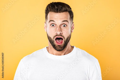 shocked handsome man in white t-shirt with open mouth isolated on yellow Canvas Print