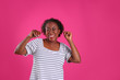 canvas print picture - Portrait of dancing African-American woman on pink background
