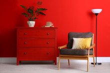 Stylish Room Interior With Modern Furniture And Houseplant Near Red Wall
