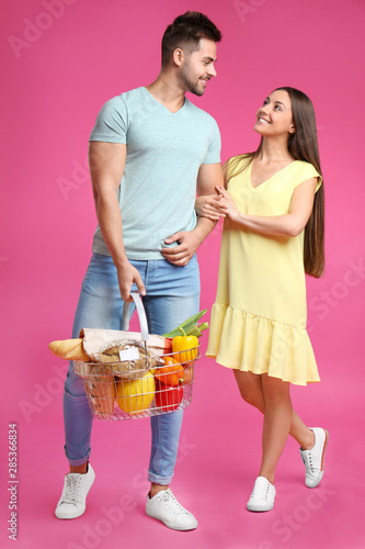 Young couple with shopping basket full of products on pink background