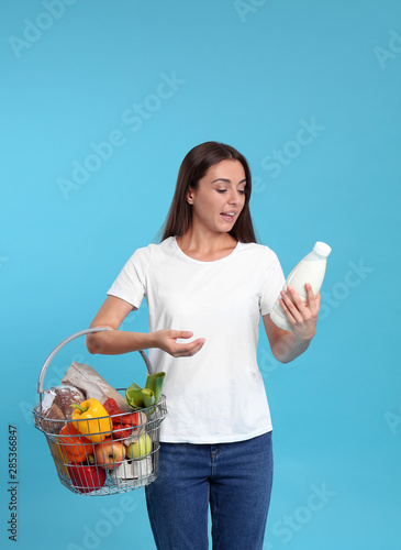 Young woman with shopping basket full of products on blue background