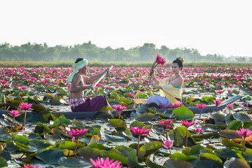 Fototapeta Orientalny Asian Men are collecting red lotus flowers for Asian women to worship. The culture of the Thai people..