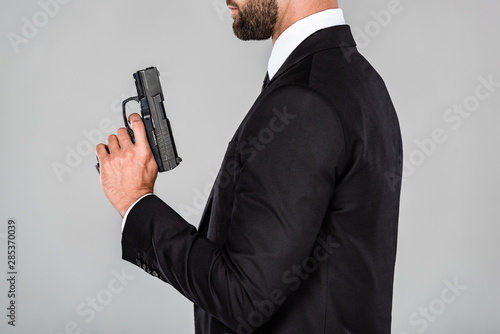 Cuadros en Lienzo cropped view of agent in black suit with gun isolated on grey