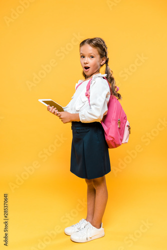 surprised schoolkid holding digital tablet with blank screen on orange