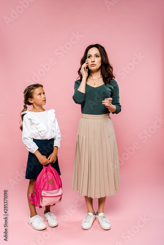 cute daughter holding backpack and looking at mother talking on smartphone on pink