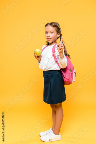 adorable schoolkid holding apple and pointing with finger on orange