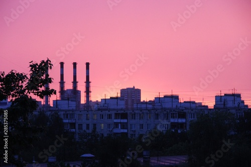 Obraz na plátně  Pink stunning sunset, urban areas, shade trees, pipe plants and silhouettes of b
