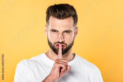 Cadres-photo bureau Pain handsome man in white t-shirt showing hush sign isolated on yellow