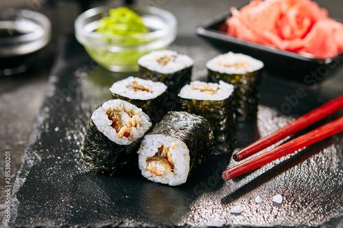 Fototapeta Macro shot of eel hosomaki sushi on natural black slate plate background with selective focus. Thin small unagi maki sushi rolls with rice, eel and nori closeup obraz